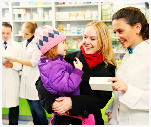 pharmacist giving a box of medicine to a mother with her daughter