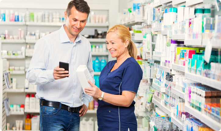 pharmacist holding a medicine while pharmacy customer is holding his phone